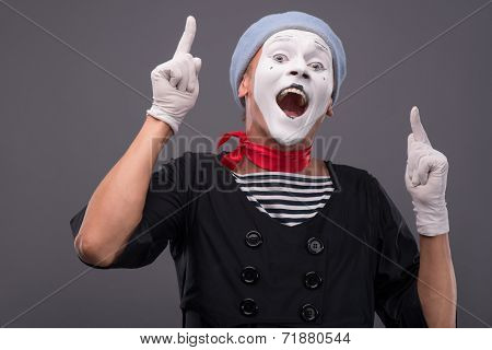 Portrait of male mime with grey hat and white face grimacing wit