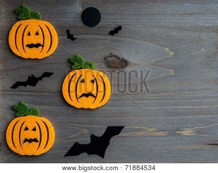 Whimsical Halloween background image of handmade felt jack-o-lantern on rustic wood
