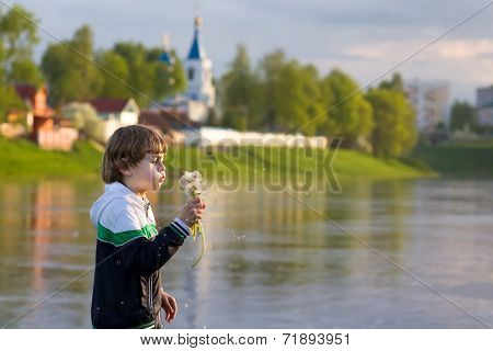 Little Boy Blowing Dandelion With Flying Seeds On Sunset Next To A Beautiful Monastery On A River Sh