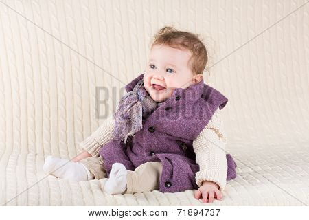 Cute Laughing Baby Girl In A Purple Jacket Sitting On A Knitted Blanket