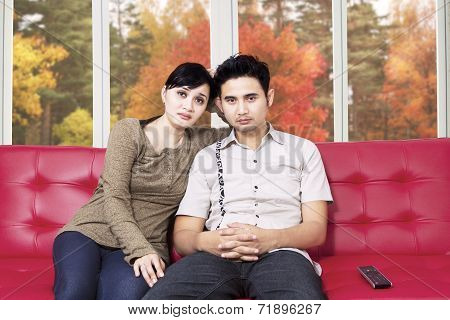 Sad Couple Watching Tv At Home