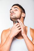 foto of electric trimmer  - young handsome man in white shirt trimming his beard with a trimmer - JPG