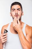 picture of electric trimmer  - young handsome man in white shirt trimming his beard with a trimmer - JPG