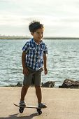 stock photo of skate board  - A young Pacific Isalnder Boy balances on his skate board  - JPG