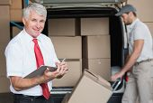 foto of warehouse  - Warehouse manager smiling at camera with delivery in background in a large warehouse - JPG