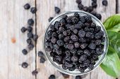 foto of chokeberry  - Ddried Chokeberries in a small bowl  - JPG
