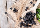 foto of chokeberry  - Wooden Spoon with dried Chokeberries on wooden background - JPG
