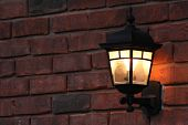 stock photo of lamp post  - A black wrought iron lamp post, with lamp light on, attached to a red bricked wall at dusk. ** Note: Shallow depth of field - JPG