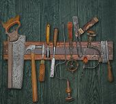 foto of wooden shack  - vintage woodworking tools on a magnetic rack against the wooden wall - JPG