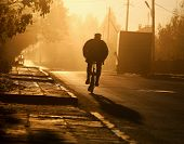 stock photo of early-man  - Man a bicycle on farm road in the early morning  - JPG