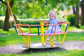image of little young child children girl toddler  - Happy laughing child beautiful little toddler girl with culy hair wearing a blue dress having fun on a playground enjoying a swing ride on a hot summer day in a sunny city park - JPG