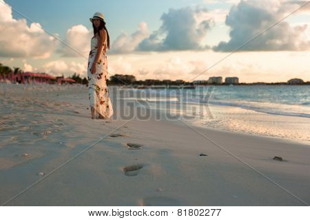 Young happy woman enjoying sunset during beach vacation