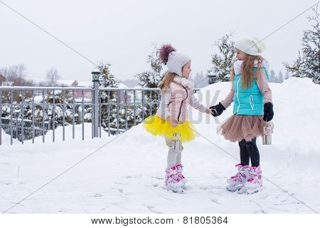 Little girls skating on ice rink outdoors in winter snow day