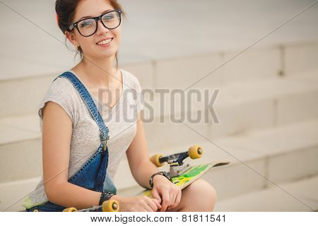 Young beautiful woman with a Board for riding on the street