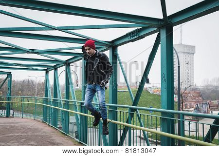 Punk Guy Jumping On A Bridge
