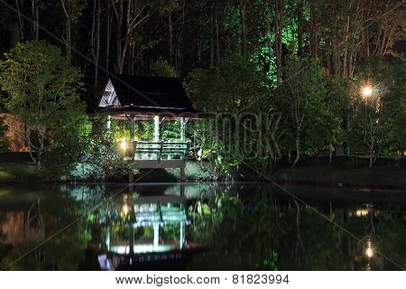 lighted arbor on the shore of lake night