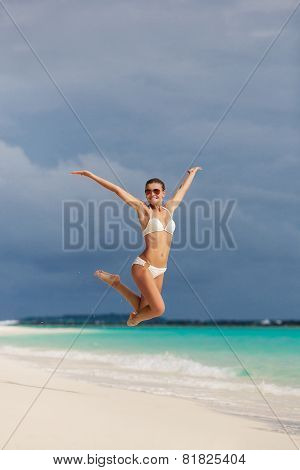 Woman jumping on the background of the beach and ocean.