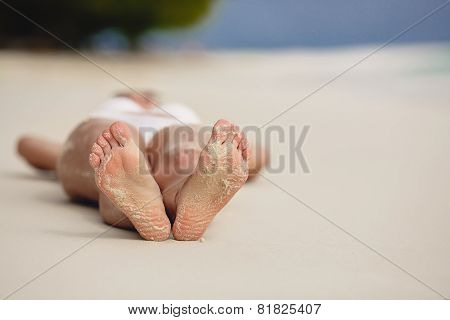 Feet of a young woman on a sandy beach.