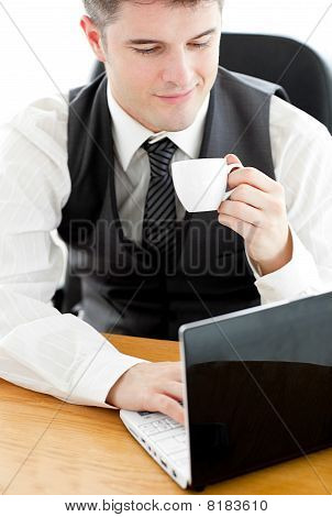 Happy Young Businessman Looking At His Laptop Holding A Coffee