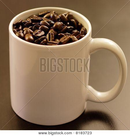 Mug full of coffee beans