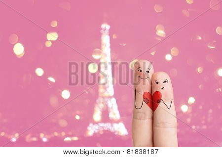 Finger art. Lovers are embracing and holding red heart against the background ?f the Eiffel tower.