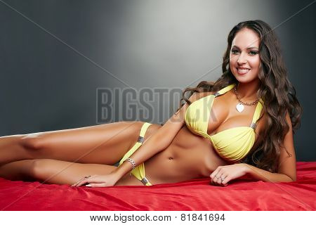 Happy attractive woman posing in yellow swimsuit