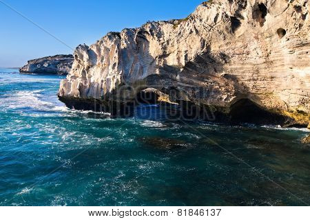 Rocky Cove And Ocean Wave Crashing Into An Eroded Arch