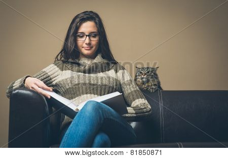 Young Woman Reading A Book With Curious Cat