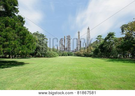 Beautiful Green Park With Oil Refinery And Smokestack In Background