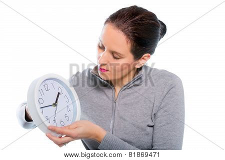 Woman setting clock at daylight savings time.