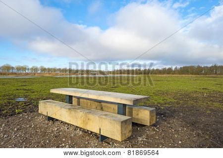Bench in a muddy field in winter