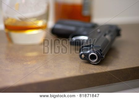 Gun, glass, bottle on the table