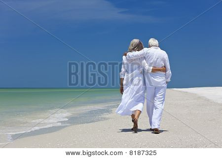 Rear View Of Senior Couple Walking Alone On A Tropical Beach