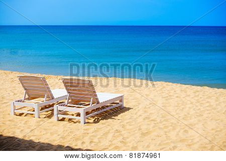 white sunbeds  on wild sea beach