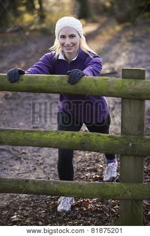 Woman Stretching On Run Through Winter Woodland