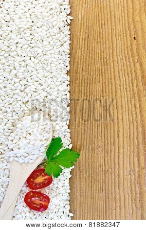 Rice white with spoon and tomatoes on board