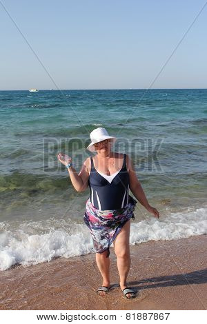 Mature woman enjoying her summer vacation frolicking in the water