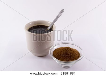 A cup of chicory and a small bowl of chicory powder with a spoon