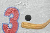 foto of hockey arena  - Hockey stick puck and the numeral three painted on the ice - JPG