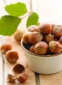 stock photo of hazelnut  - natural organic hazelnuts in a bowl on the table - JPG