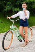 pic of walking away  - Full length of attractive young smiling woman drinking coffee and looking away while walking with her bicycle in park - JPG