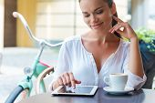 picture of toothless smile  - Attractive young woman working on digital tablet and smiling while sitting at the sidewalk cafe - JPG