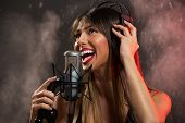 stock photo of singer  - Portrait of a young woman singer with headphones in front of the microphone - JPG
