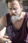 pic of hillbilly  - A young man sitting outside a abandoned house and smoke cigarettes - JPG