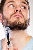 pic of razor  - Health beauty and skin care concept. Closeup of male face. Young man guy styling beard holding disposable blue razor blade white background.