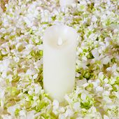 stock photo of san valentine  - The big white candle in a wreath from artificial flowers - JPG