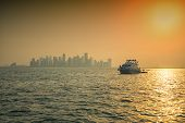 foto of leaving  - boat leaving the city in the sunset