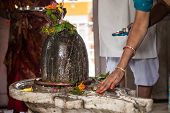 picture of lingam  - Hindu devotees bathe a shiva - JPG