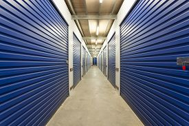 stock photo of warehouse  - Warehouse with roller doors and private storage sheds - JPG