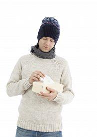 stock photo of tissue box  - Adult man having a flu taking tissue from tissue box - JPG